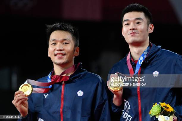 Taiwan's Lee Yang and Taiwan's Wang Chi-lin pose with their men's doubles badminton gold medals at a ceremony during the Tokyo 2020 Olympic Games at...