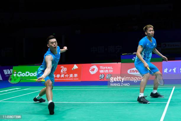 Taiwan's Lee Yang and Wang ChiLin hit a return against Indonesia's Marcus Fernaldi Gideon and Kevin Sanjaya Sukamuljo during their men's doubles...