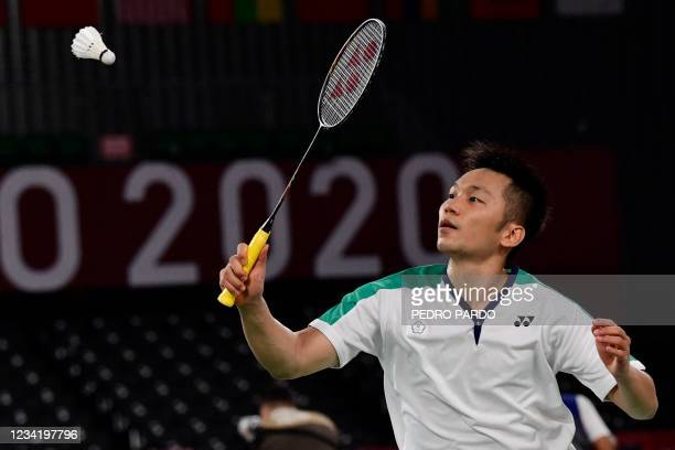 Taiwan's Lee Yang hits a shot next to Taiwan's Wang Chi-lin in their men's doubles badminton group stage match against Britain's Sean Vendy and...