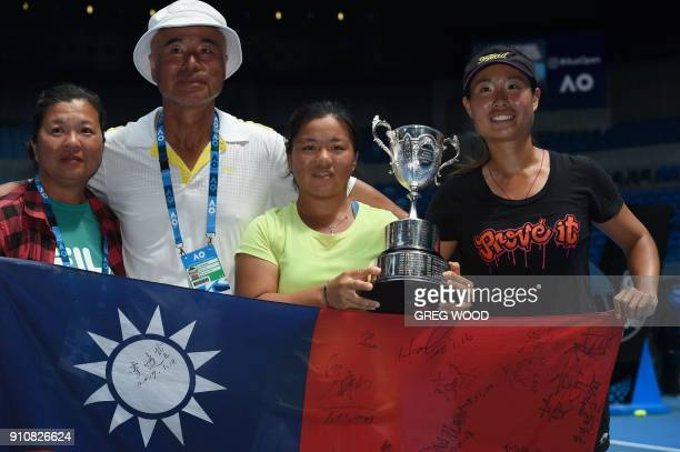 Taiwan's Liang En Shuo poses with the winner's trophy and her mother Hsia Pi Ying and coaches Chan FoCheng and Chan ChinWei after beating France's...