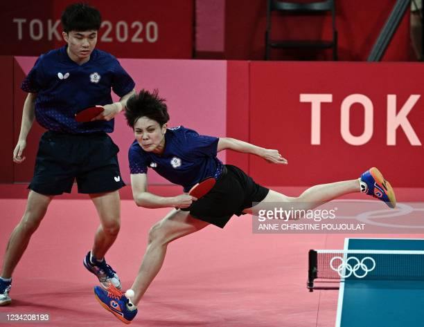 Taiwan's Lin Yun-ju looks at Cheng I-ching hitting a shot against France's Emmanuel Lebesson and Jia Nan Yuan in the mixed doubles table tennis match...