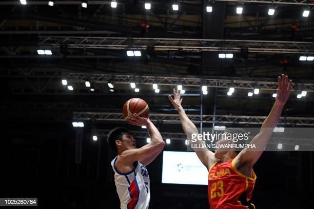 Taiwan's Liu Cheng shoots against China's Abudushalamu Abudurexiti in the men's basketball semifinal match between China and Taiwan during the 2018...