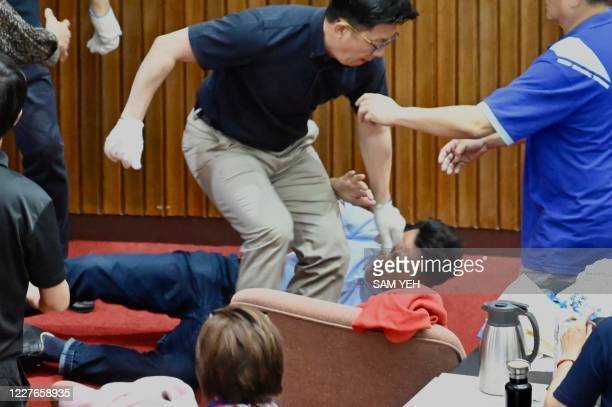 Taiwans main opposition Kuomintang legislator Lu Ming-che falls on the ground as the KMT protest against Taiwan President Tsai Ing-wen's nomination...