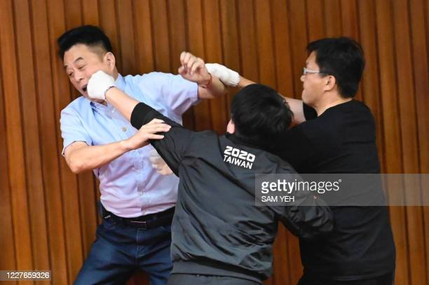TOPSHOT Taiwans main opposition Kuomintang legislator Lu Mingche L fights with ruling Democratic Progressive Party lawmaker Wu Pingjui as the KMT...
