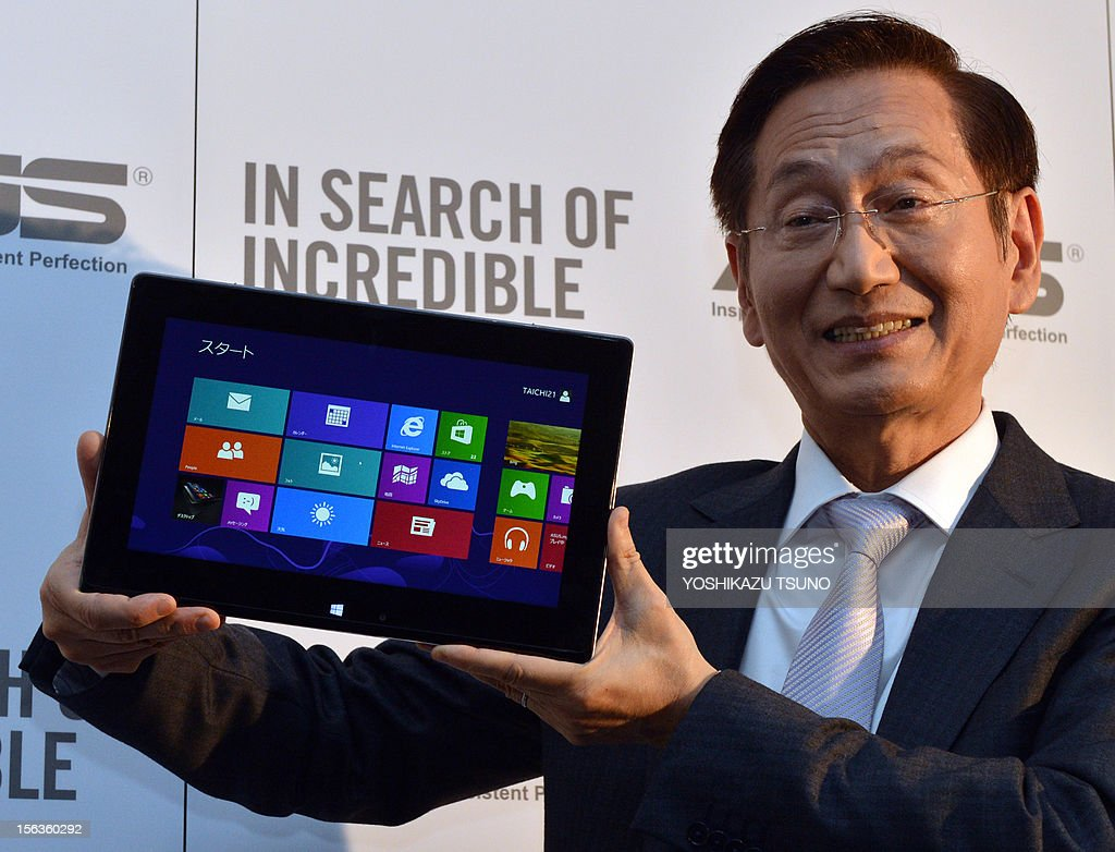 Taiwan's personal computer giant ASUS chairman Honney Shih displays the world's first dual screens notebook computer 'Taichi', which has 11.6-inch LCD display on the both side, enabling to use as a tablet and notebook computer in Tokyo on November 14, 2012. The unique PC, equipped with Intel's Core i7 processor on its CPU will go on sale December 8. AFP PHOTO / Yoshikazu TSUNO