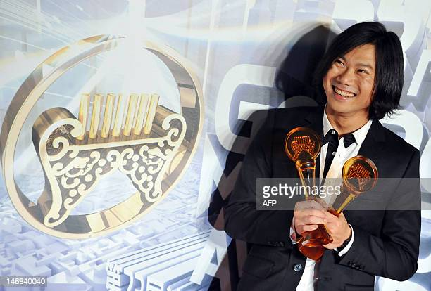 Taiwan's pop music group Mayday's Bassist Matthew Tsai smiles with the trophies after winning best band best composer best album producer best...