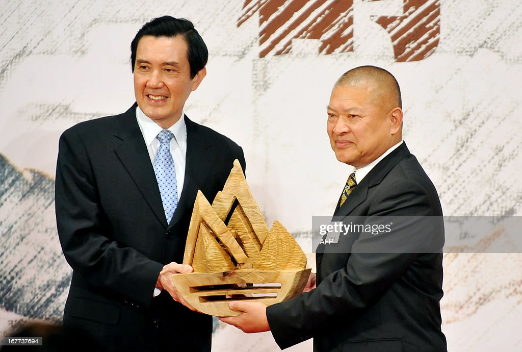 Taiwan's President Ma Ying-jeou (L) confers a gift to Wang Zhihzhong, son of former Chinese chief negotiator in talks with Taiwan Wang Daohan, during a ceremony held at the headquarters of the island's quasi-official Straits Exchange Foundation in Taipei on April 29, 2013. Ma renewed the 'one China' policy of his government as Taiwan marked the 20th anniversary of the of the first high-level talks between Taiwan and the Chinese mainland since their split in 1949 at the end of a civil war. AFP PHOTO / Mandy CHENG