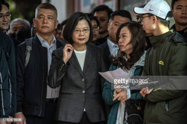 Taiwans President Tsai Ing-wen gestures as she talks to voters while queueing to vote in the presidential election on January 11, 2020 in Taipei,...