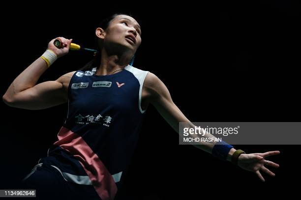 Taiwan's Tai Tzu Ying hits a return against Thailand's Ratchanok Intanon during their women's singles quarterfinal match at the Malaysia Open...