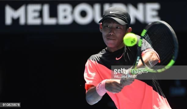 Taiwan's Tseng Chun Hsin hits a return against Sebastian Korda of the US during their junior boys' singles final match on day 13 of the Australian...