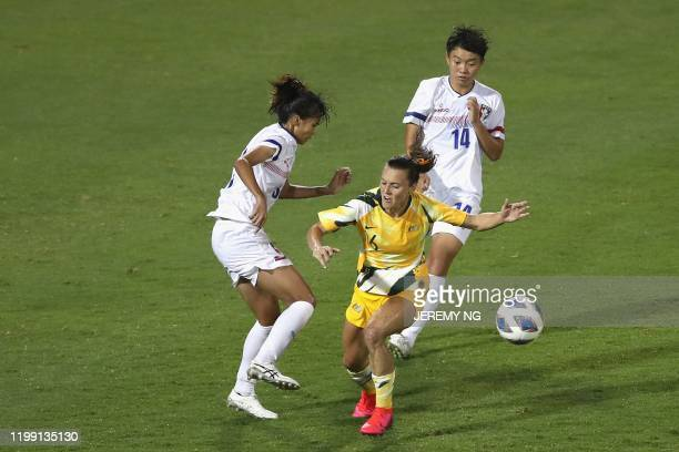 Taiwan's Wang Hsiang-huei and Lan Yu-chieh tackle Australia's Hayley Raso during the women's Olympic football tournament qualifier match between...