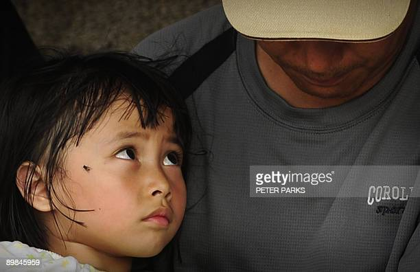 TaiwanweathertyphoonaboriginesFOCUS by Polly Hui An aboriginal girl looks up at her father as they wait for relatives to return at the typhoon rescue...