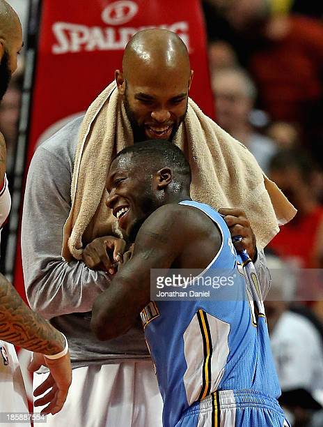 Taj Gibson of the Chicago Bulls and Nate Robinson of the Denver Nuggets share a laugh and a hug after a preseason game at the United Center on...