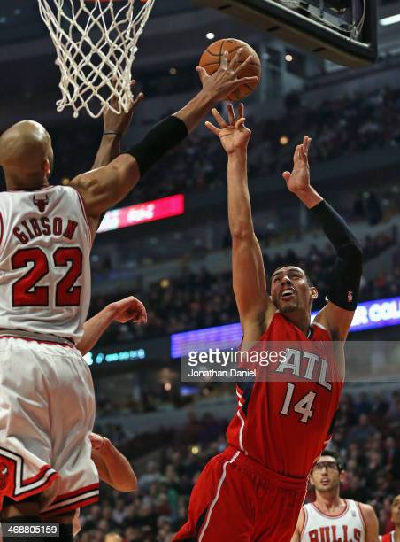 Taj Gibson of the Chicago Bulls blocks a shot by Gustavo Ayon of the Atlanta Hawks at the United Center on February 11 2014 in Chicago Illinois NOTE...