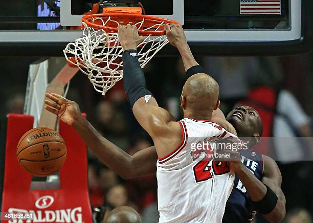 Taj Gibson of the Chicago Bulls dunks against Bismack Biyombo of the Charlotte Bobcats at the United Center on January 11 2014 in Chicago Illinois...