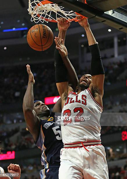 Taj Gibson of the Chicago Bulls dunks over Zach Randolph of the Memphis Grizzlies at the United Center on March 7 2014 in Chicago Illinois The...