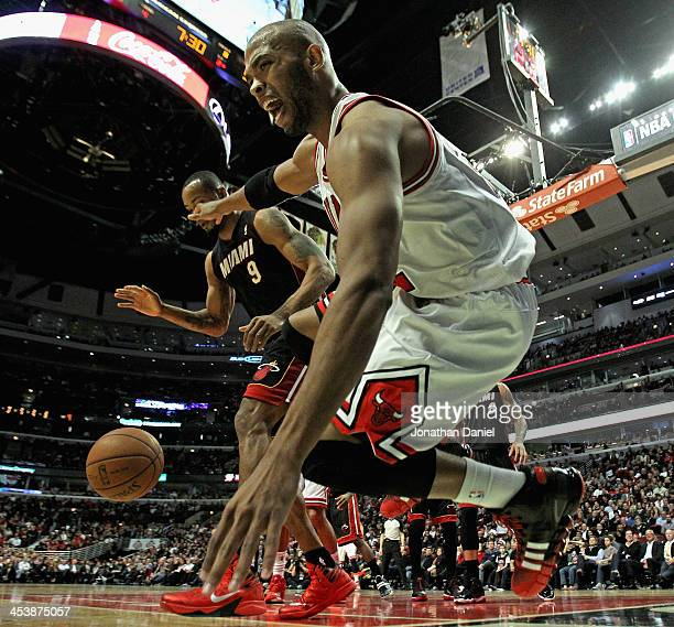 Taj Gibson of the Chicago Bulls falls out of bounds trying for a loose ball under poressure from Rashard Lewis of the Miami Heat at the United Center...