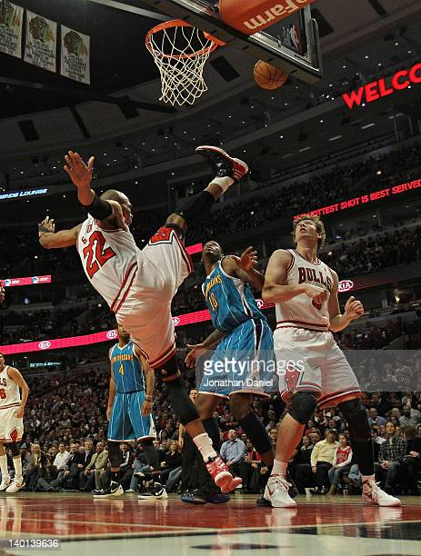 Taj Gibson of the Chicago Bulls falls to the floor after taking a shot against Solomon Jones of the New Orleans Hornets as Omer Asik gets into...