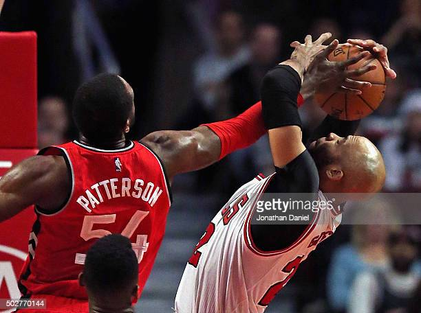 Taj Gibson of the Chicago Bulls grabs a rebound away from Patrick Patterson of the Toronto Raptors at the United Center on December 28 2015 in...