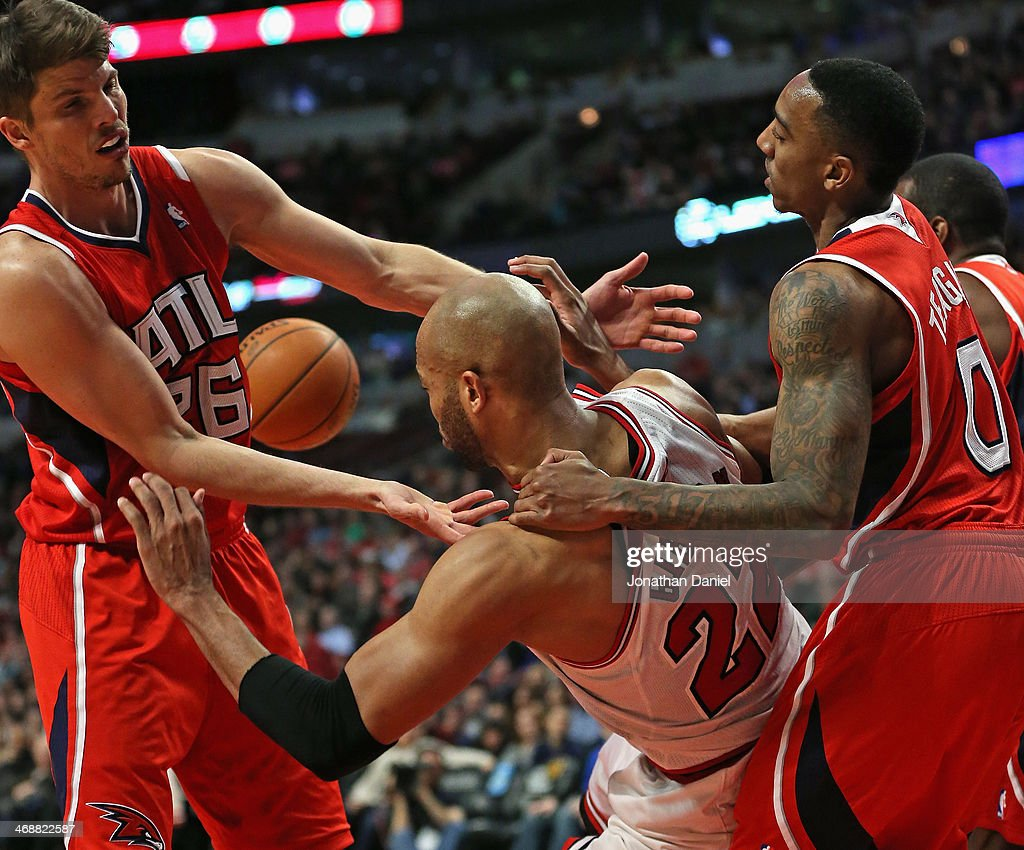Taj Gibson #22 of the Chicago Bulls is pulled to the ground by Jeff Teague #0 of the Atlanta Hawks for a flagrant foul as Kyle Korver #26 tries for the ball at the United Center on February 11, 2014 in Chicago, Illinois. The Bulls defeated the Hawks 100-85.