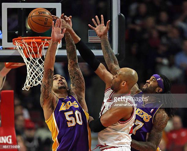 Taj Gibson of the Chicago Bulls puts in a shot between Robert Sacre and Jordan Hill of the Los Angeles Lakers at the United Center on January 20 2014...