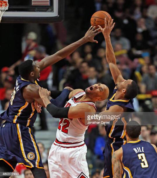 Taj Gibson of the Chicago Bulls reacts after getting hit as Ian Mahinmi and Evan Turner of the Indiana Pacers try for a rebound at the United Center...