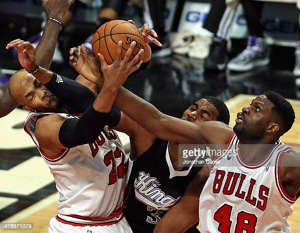 Taj Gibson of the Chicago Bulls rebounds over teammate Nazr Mohammed and Jason Thompson of the Sacramento Kings at the United Center on March 15 2014...
