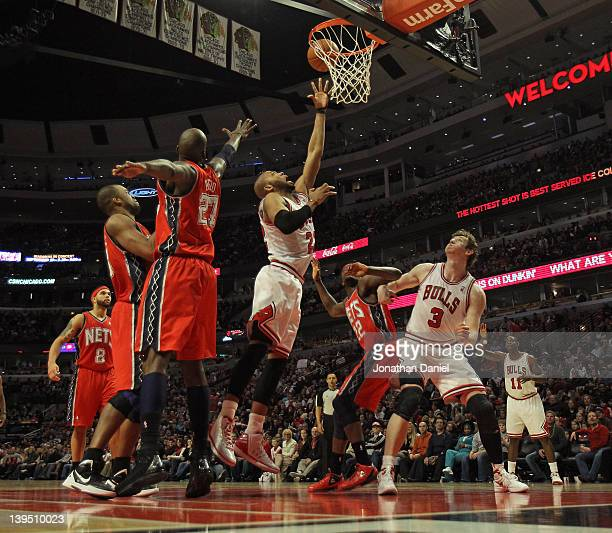 Taj Gibson of the Chicago Bulls shoots over teammate Omer Asik and Anthony Morrow of the New Jersey Nets at the United Center on February 18 2012 in...