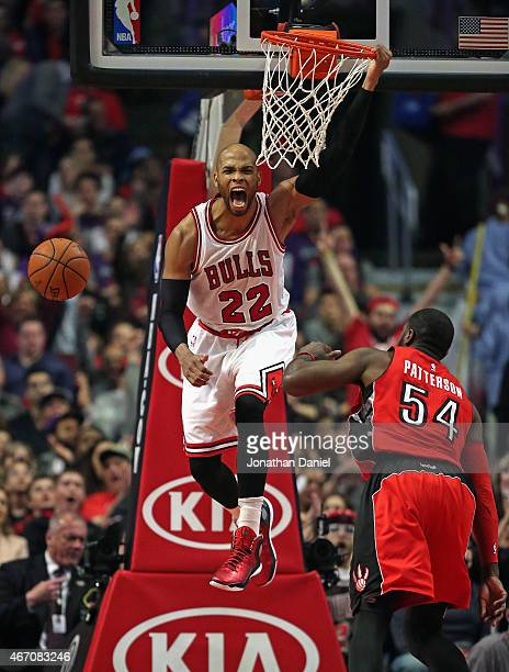 Taj Gibson of the Chicago Bulls yells as he dunks over Patrick Patterson of the Toronto Raptors in his first game back from injury at the United...