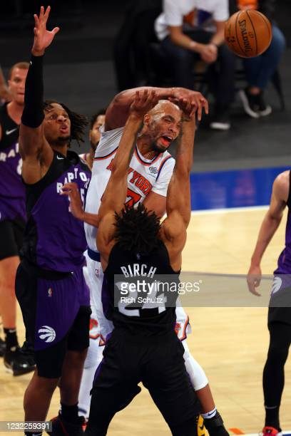 Taj Gibson of the New York Knicks attempts a shot as Freddie Gillespie and Khem Birch of the Toronto Raptors defend at Madison Square Garden on April...