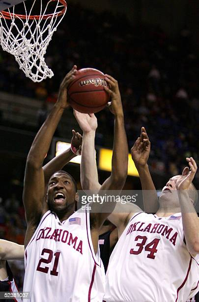 Taj Gray of the Oklahoma Sooners grabs a rebound in front of teammate Kevin Bookout in the first half against the Texas Tech Red Raiders in the...