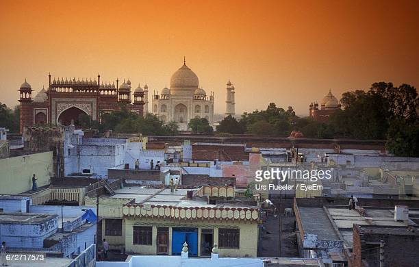 Taj Mahal And Houses Against Sky During Sunset