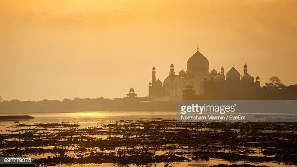 Taj Mahal By Yamuna River Against Sky During Sunrise
