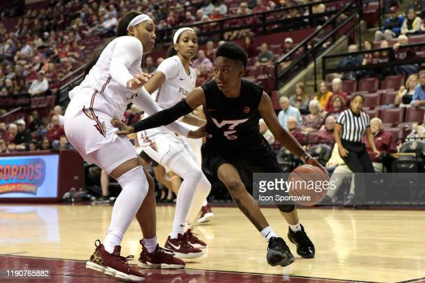 Taja Cole guard Virginia Tech Hokies drives the baseline against a double-team of Kiah Gillespie forward and Morgan Jones guard Florida State...