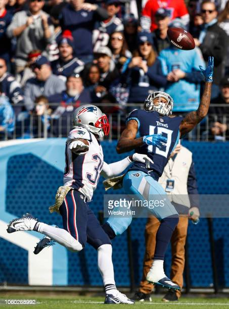 Tajae Sharpe of the Tennessee Titans reaches for a pass from Marcus Mariota while defended by Jason McCourty of the New England Patriots during the...