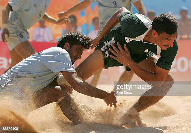 Tajammal Muhammad of Pakistan is tackled by India during their beach kabaddi match on day five of the 2008 Asian Beach Games at Nusa Dua Beach on...
