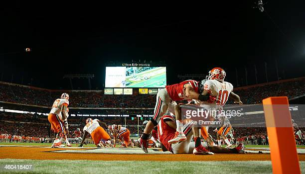 Tajh Boyd of the Clemson Tigers throws the ball away and is called for intentional grounding resulting in a safety as Joey Bosa and Joshua Perry of...