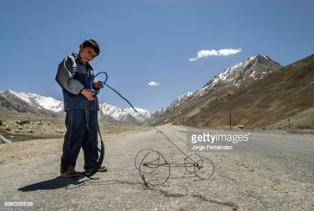 Tajik boy playing with an very basic toy car made out of wire