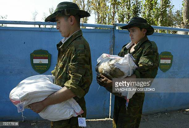 Tajik frontier guard soldiers carry bags with opium captured whilst patroling the Afghan border not far from the town of Pyandj some 220 km from...