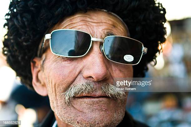 Tajik man wearing a traditional Tajik hat and Made in China fake sunglasses Tashkurgan Xinjiang China