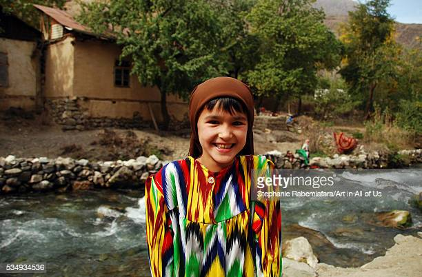 Tajikistan Penjakent portrait of local girl in traditional dress by the river