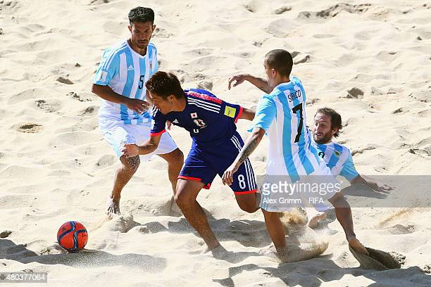 Takaaki Oba of Japan is challenged by Rodrigo Lopez Luciano Sirico and Federico Hilaire of Argentina during the FIFA Beach Soccer World Cup Portugal...