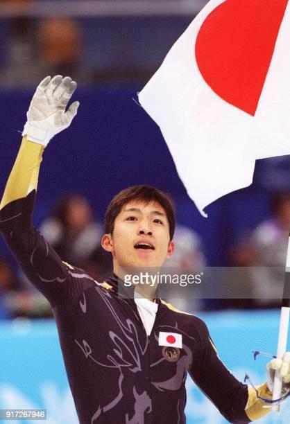 Takafumi Nishitani of Japan waves the Japanese flag after winning the men's Olympic 500m shorttrack speed skating in Nagano 21 February / AFP PHOTO /