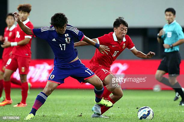 Takagi Akito of Japan vies with Cao Yongjing of China during a match between China and Japan of 2015 'Changan Ford Cup' CFA International Youth...