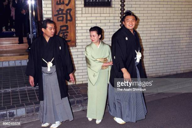 Takahanada celebrates winning the tournament with his father and stable master Fujishima and his mother in front of the stable after day fifteen of...