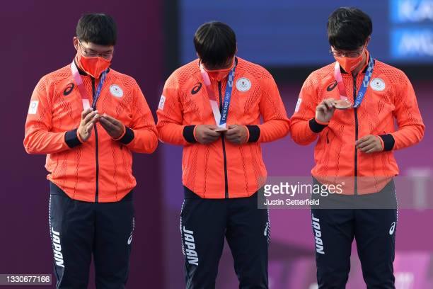 Takaharu Furukawa, Yuki Kawata, and Hiroki Muto of Team Japan react on the medal stand after receiving their bronze medals in the Men's Team...