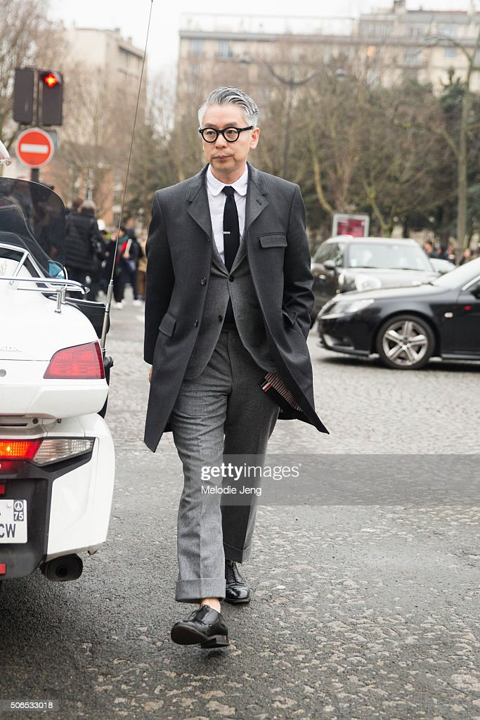 Takahiro Kinoshita, Popeye Magazine Editor-in-Chief exits the Dior Homme show in a gray suit and jacket on January 23, 2016 in Paris, France.