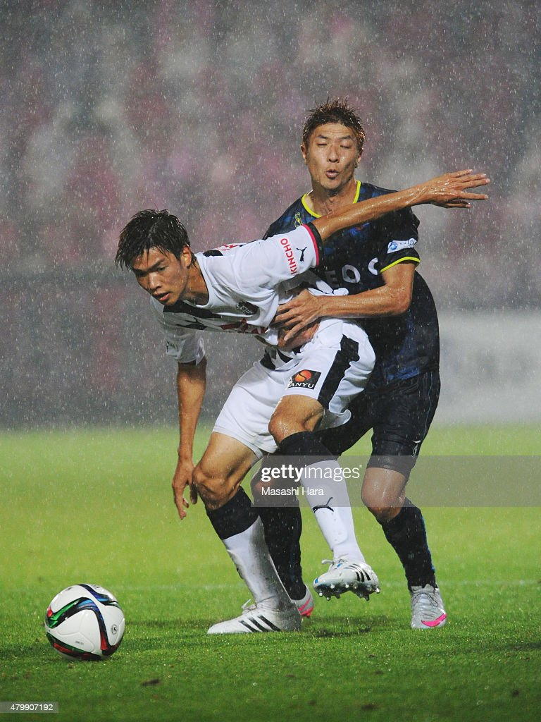 Takahiro Ogihara #2 of Cerezo Osaka (L) and Masaru Kurotsu compete for the ball during the J.League second division match between Yokohama FC and Cerezo Osaka at Nippatsu Mitsuzawa Stadium on July 8, 2015 in Yokohama, Kanagawa, Japan.