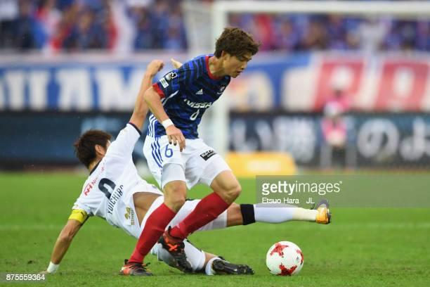 Takahiro Ogihara of Yokohama FMarinos is tackled by Yoichiro Kakitani of Cerezo Osaka during the JLeague J1 match between Yokohama FMarinos and...