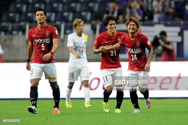 Takahiro Sekine of Urawa Red Diamonds celebrates scoring his team's first goal with his team mate Toshiyuki Takagi during the JLeague match between...